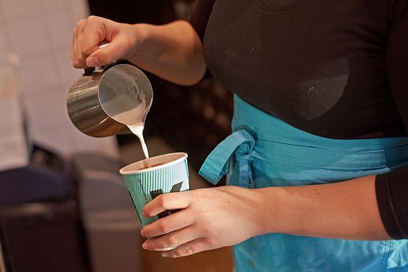 Kahvilatyöntekijä kaataa maitoa kahviin.