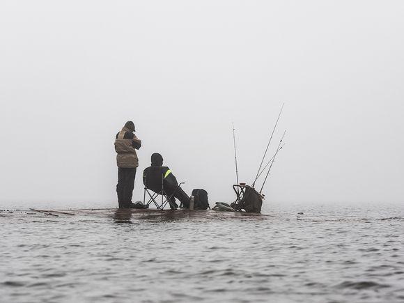 Kaksi miestä kalastaa sumun keskellä.