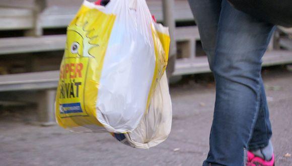 ihminen kulkee muovikassi kädessä