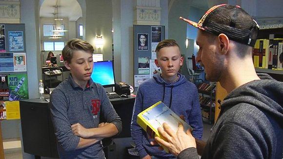 Video: Mies esittelee kirjaa kahdelle pojalle kirjastossa.