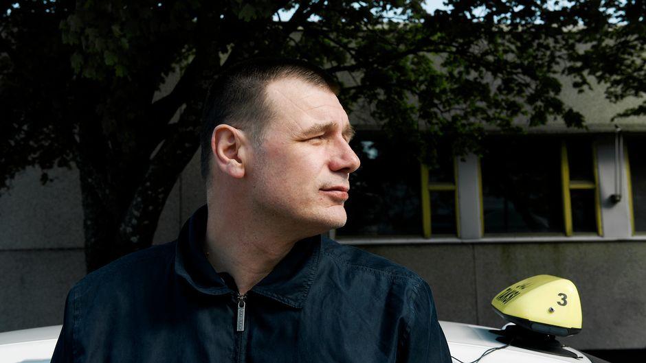 Tummaan asuun pukeutunut Vilho Sakari Leino nojaa valkoiseen taksiautoon.