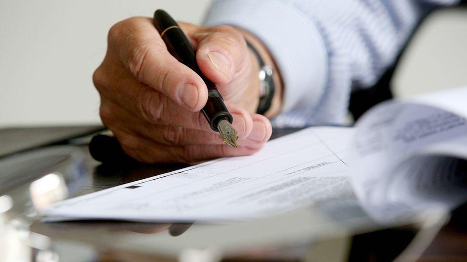 Käsi allekirjoittaa mustekynällä.