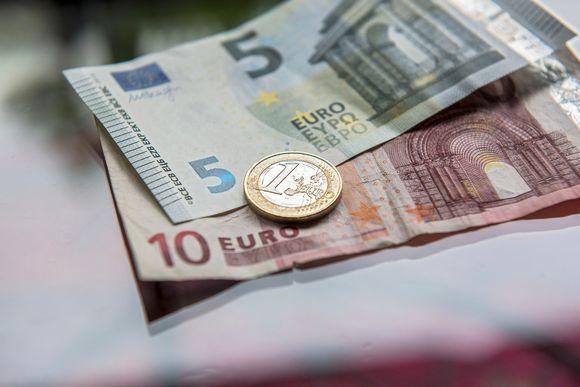 Seteleitä ja euron kolikko pöydällä.