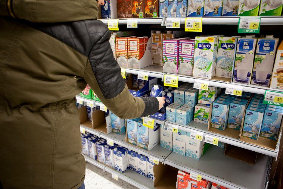 Nainen marketin maitohyllyllä.