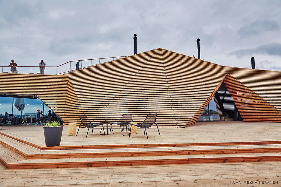 Turisteja saunan katolla ja saunan edessä tuoleja