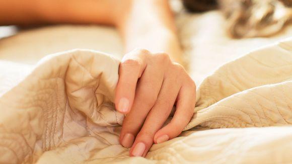 Naisen käsi sängyllä.