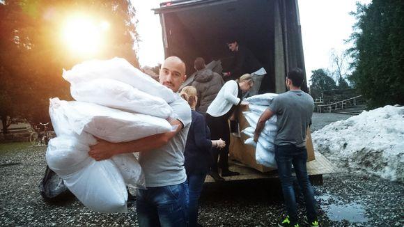 Miehiä kantamassa tyynyjä.