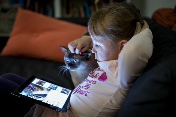 Viisivuotias Kaisla katselee iPadia, kuvassa myös perheen kissa.