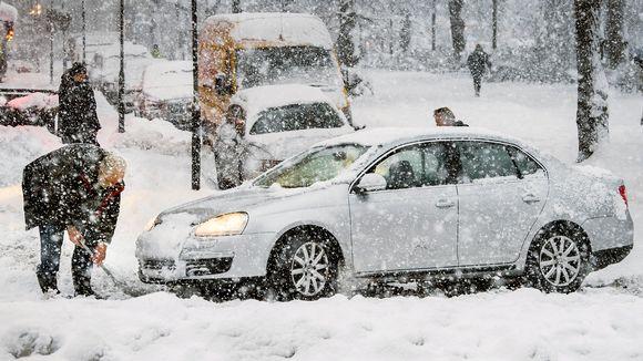 Mies lapioi lunta auton edessä lumimyrskyssä.