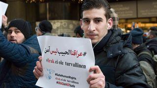 Mies pitää lappua käsissään jossa lukee ettei Irak ole turvallinen.