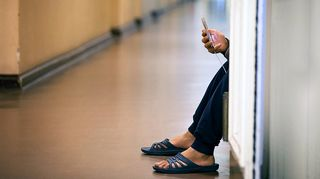 Turvapaikanhakija käyttää kännykkää käytävällä