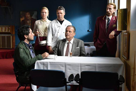 Kaksi miestä istuu ravintolan pöydässä, kokki, tarjoilija ja ovimies katselevat heitä.