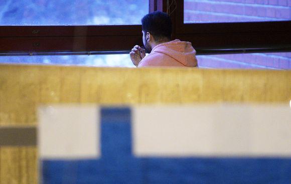 Turvapaikanhakija ikkunan äärellä.