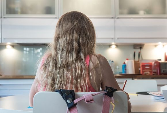 Tyttö istuu keittiön pöydän ääressä selin kameraan.