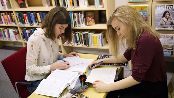 Kaksi abiturienttia kirjastossa.