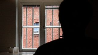 Vanki katselee ulos kalteri-ikkunasta