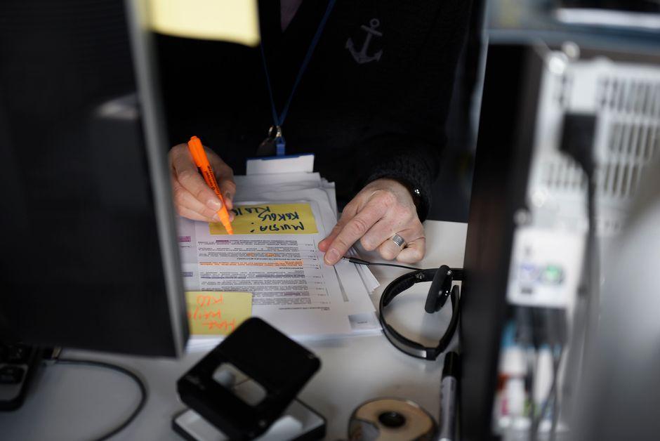 Työntekijä alleviivaa tekstiä työpöytänsä ääressä.