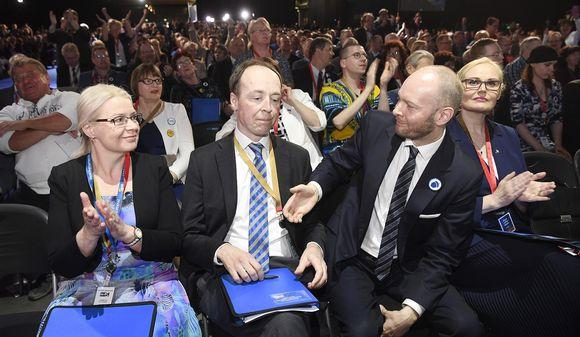 Sampo Terho ja Leena Meri onnittelevat puolueen uutta puheenjohtajaa Jussi Halla-ahoa perussuomalaisten puoluekokouksessa Jyväskylässä.