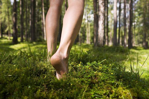 Paljain jaloin metsässä.