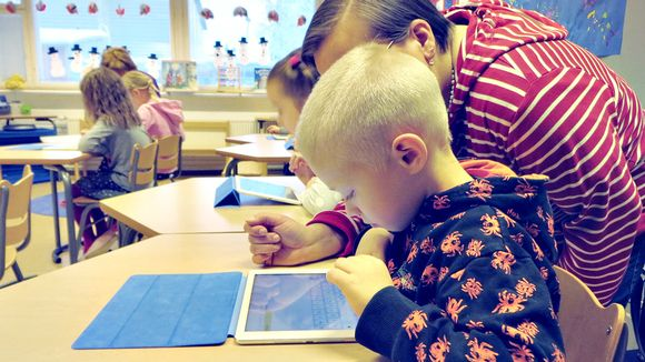 Lapsi käyttää tablettitietokonetta.