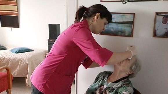 Hoitaja laittaa silmätippoja vanhukselle.