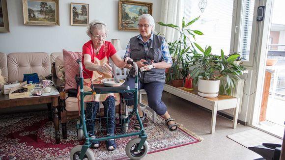 Lähihoitaja Leila Kantanen katsoo vierestä kun Sirkka Arola ruokailee kotonaan.
