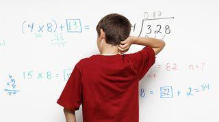 Poika laskee koulutehtävää taululla.