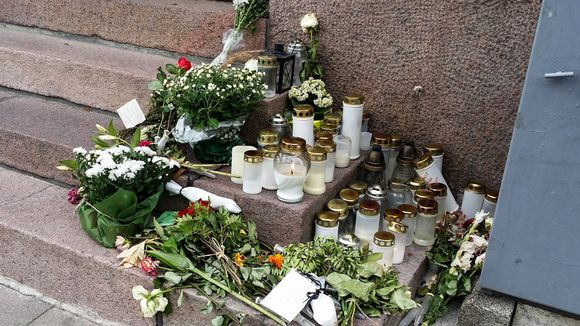 Turun toisen puukotuksen uhrin tapahtumapaikalle tuotuja kukkia ja kynttilöitä.