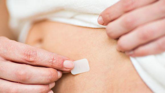 nainen laittaa hormonilaastarin ihoon.