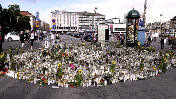 Muistokynttilöitä ja kukkia joukkopuukotuspaikalla Turun kauppatorilla