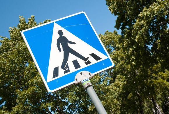 Suojatie-merkki, jossa kuvattuna mies ylittämässä katua.