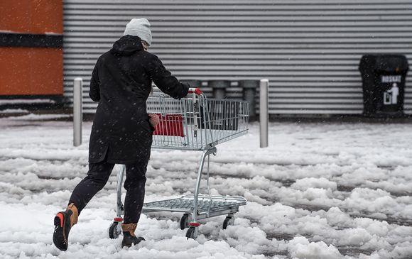 Nainen työntää ostoskärryjä lumisohjoisella parkkipaikalla.