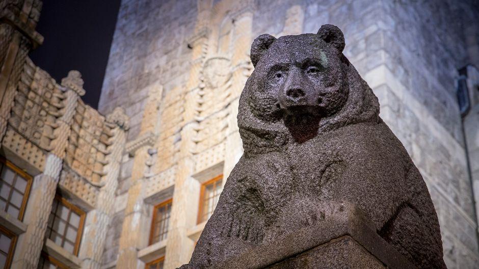 Suomen kansallismuseo iltavalaistuksessa, kuvassa karhu-patsas etualalla.