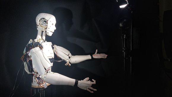 Humanoidirobotti ojentaa käsiään valoa kohti