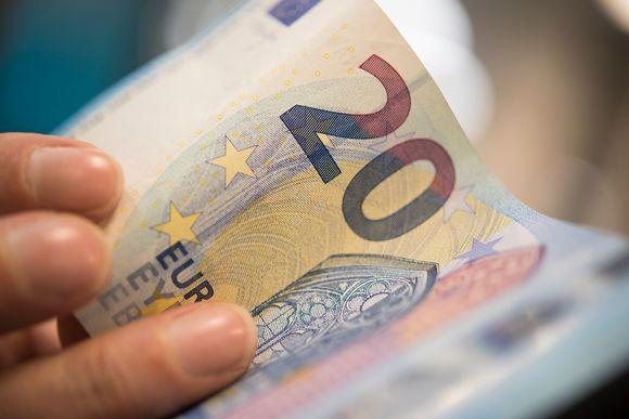 Miehen kädessä kahdenkymmenen euron seteli.