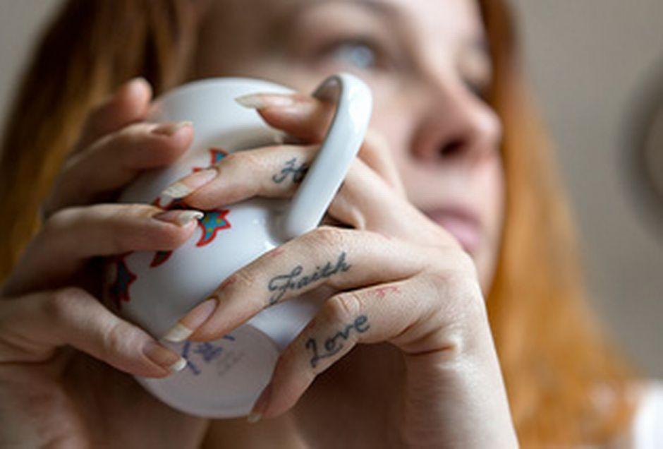 Love ja Faith -tatuoinnit sormissa