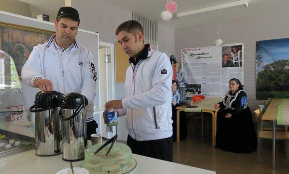 Kaksi miestä ottaa tiskiltä kahvia.