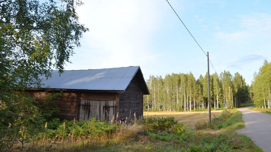 Huonokuntoinen lato kapean asfaltoidun tien varressa, pellon laidalla Virolahdella.