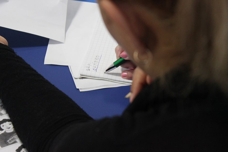 Nainen kirjoittaa maahanmuuttajaäitien kielikurssilla Kotkassa.