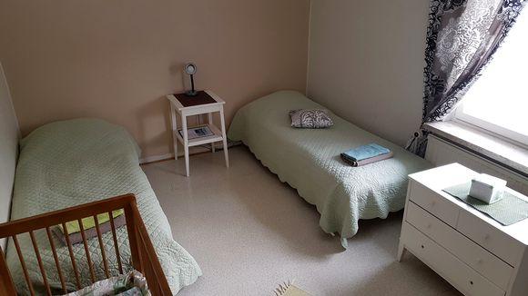 Kaksi sänkyä ja pinnasänkyä turvakodin perhehuoneessa