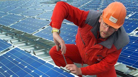 Mies asentaa aurinkopaneeleita