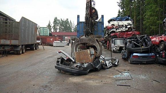 Autoa rutataan raskaalla metallipainolla.