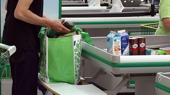 Ihminen pakkaa ruokia kassiin kaupan kassalla.
