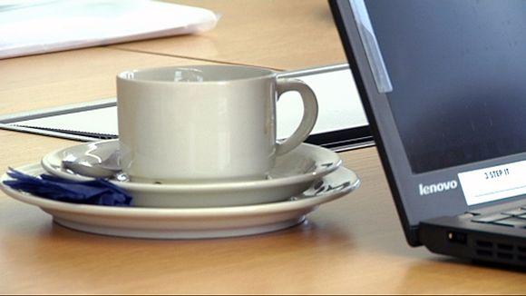Kahvikuppi ja tietokone pöydällä.