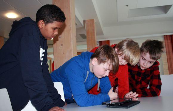 Oppilaat työskentelevät tabletilla.