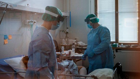 Kaksi hoitajaa ja potilas koronaosastolla Helsingissä