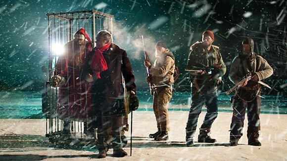 Kuvassa häkkiin vangittu joulupukki sekä näyttelijät Per Christian Ellefsen, Rauno Juvonen, Tommi Korpela ja Jorma Tommila lumisateessa.