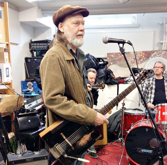 Tuomari Nurmio eläytyy treenikämpällä Judge Bonen rooliin. Taustalla Hoedown-yhtyeen rumpali Topi Kurki (oik) ja basisti Masa Maijanen.