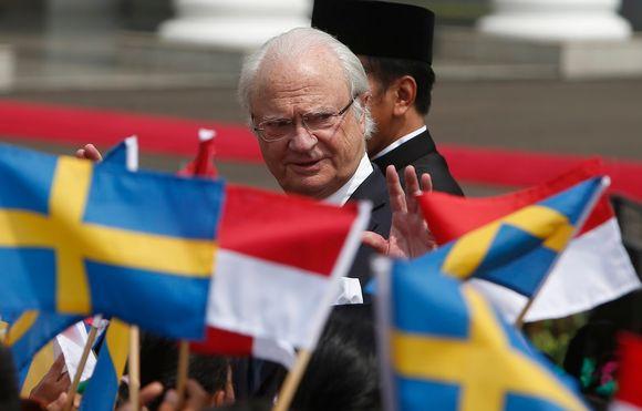 Kuningas vilkuttaa lapsille, jotka heiluttavat Ruotsin ja Indonesian lippuja.