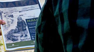 Näyttelyjulisteessa on piirroskuva tielle kuolleesta naisesta ja hänen vieressään seisovasta lapsesta; taustalla jono muita nälkäpakolaisia.